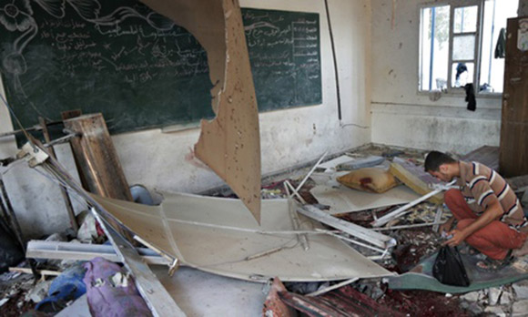 A Palestinian collects body parts in a classroom at the Abu Hussein UN school.