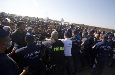 Hungarian police officers stop a group of migrants near a makeshift camp for asylum seekers in Roszke, southern Hungary, Wednesday, Sept. 9, 2015. Leaders of the United Nations refugee agency warned Tuesday that Hungary faces a bigger wave of 42,000 asylum seekers in the next 10 days and will need international help to provide shelter on its border, where newcomers already are complaining bitterly about being left to sleep in frigid fields. (AP Photo/Darko Vojinovic)